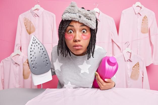 Une femme afro-américaine choquée regarde très surprise par la caméra occupée à repasser des vêtements après la lessive, une bouteille de détergent et un fer électrique portent un masque de sommeil, un pyjama doux reste à la maison pendant la quarantaine
