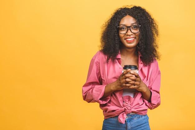 Femme afro-américaine avec une coiffure afro à côté tout en buvant du café à emporter dans une tasse en papier