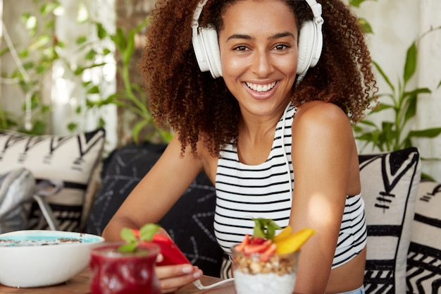 Une femme afro-américaine avec une coiffure bouclée et touffue partage des médias sur les réseaux sociaux, utilise une connexion internet gratuite pour discuter avec des amis et écouter de la musique préférée dans des écouteurs. concept de loisirs