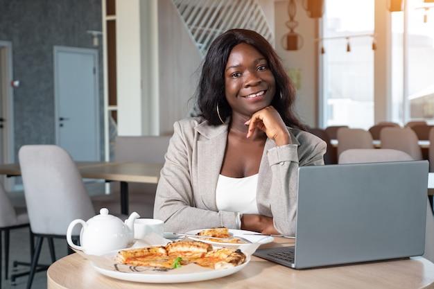 Femme afro-américaine en costume d'affaires avec ordinateur portable et pizza au café