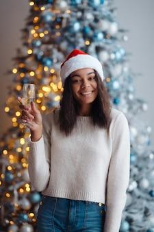 Femme afro-américaine avec une coupe de champagne à la maison. célébration de noël