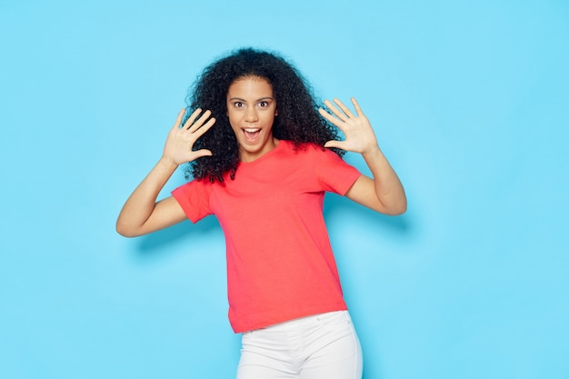 Femme afro-américaine dans un t-shirt sur un fond coloré posant