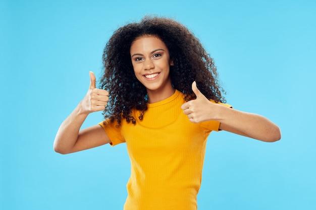 Femme afro-américaine dans un t-shirt en studio sur une surface colorée posant
