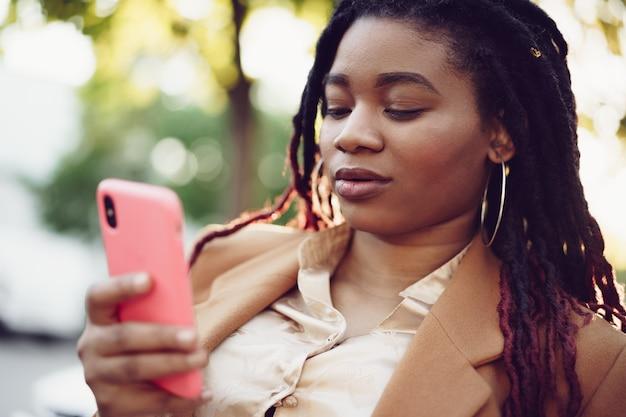 Femme afro-américaine debout dans une rue et utilisant un smartphone
