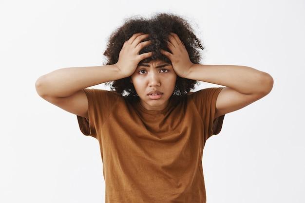 Femme afro-américaine déprimée et fatiguée avec une coiffure afro se sentant ennuyée et épuisée par des troubles sur la tête en fronçant les sourcils se tenant la main sur les cheveux