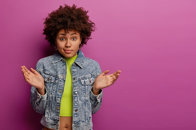 Une femme afro-américaine douteuse et désemparée écarte les paumes avec hésitation, ne peut pas prendre de décision, porte une veste et un haut en jean, a un regard perplexe, pose sur un mur violet vibrant, espace de copie de côté