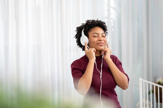 Femme afro-américaine écoutant de la musique avec ses écouteurs dans le salon