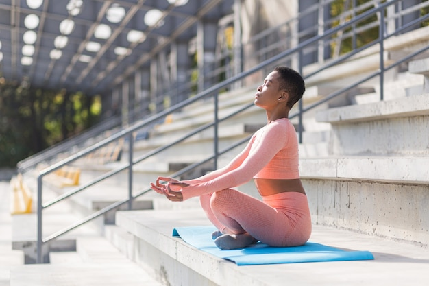 Une femme afro-américaine effectue des exercices de respiration assise sur un tapis de yoga dans le parc près du stade, se reposant après l'entraînement