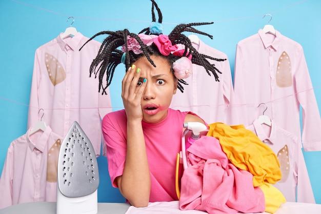 Une femme afro-américaine effrayée couvre la main avec des poses de visage près d'une pile de linge déplié ne veut pas laver les tâches ménagères pose contre le mur bleu