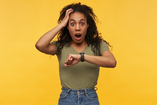 Une femme afro-américaine étonnée et choquée garde sa main sur la tête, regardant la caméra avec une expression faciale stressée.