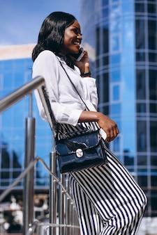 Femme afro-américaine à l'extérieur par le gratte-ciel avec téléphone