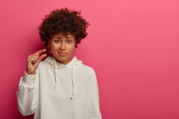 Femme afro-américaine façonne un objet petit ou minuscule, exprime le dédain