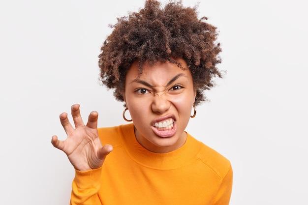 Une femme afro-américaine fait une grimace le visage effrayant tient la main comme si la griffe serrait les dents voulait effrayer l'enfant raconte une histoire d'horreur porte des vêtements décontractés isolés sur un mur blanc grogne comme un animal