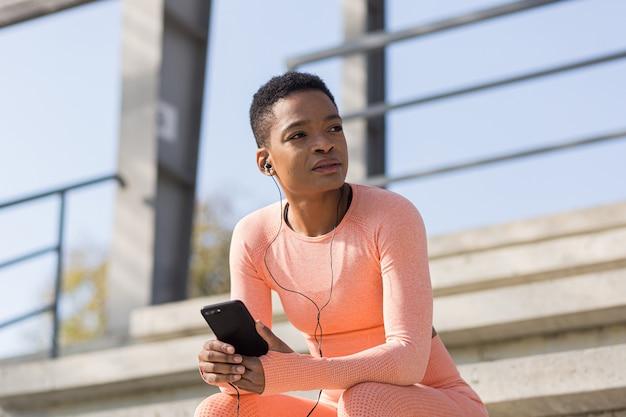 Femme afro-américaine fatiguée après l'entraînement en écoutant de la musique et un podcast audio, après avoir fait du jogging et s'être entraîné au stade le matin