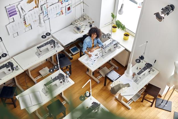 Une femme afro-américaine gaie dessine de nouveaux vêtements dans un carnet de croquis près de la machine à coudre dans un studio spacieux