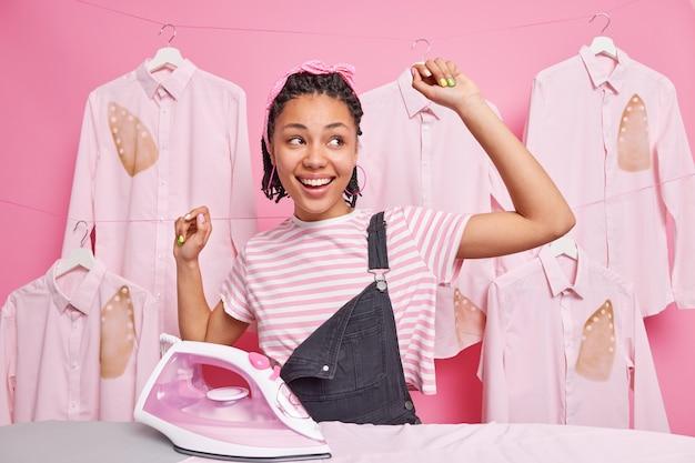 Une femme afro-américaine gaie et insouciante avec des dreadlocks et des danses de peau foncée près d'une planche à repasser garde les bras levés, des sourires largement heureux de terminer les travaux ménagers à temps pose contre des chemises sur des cintres autour