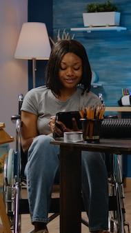 Femme afro-américaine handicapée tenant une tablette numérique