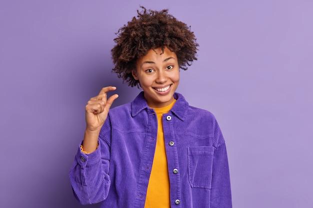 Une femme afro-américaine heureuse aux cheveux bouclés montre des stands de petite taille joyeux montre une petite chose ou un objet vêtu d'une veste de velours pose contre un mur violet. concept de langage corporel