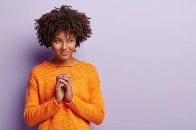 Une femme afro-américaine heureuse invente un plan, a un regard intrigant de côté sur l'espace libre, garde les paumes jointes, détourne le regard, porte un pull orange, isolé sur un mur violet. personnes, concept d'intention.