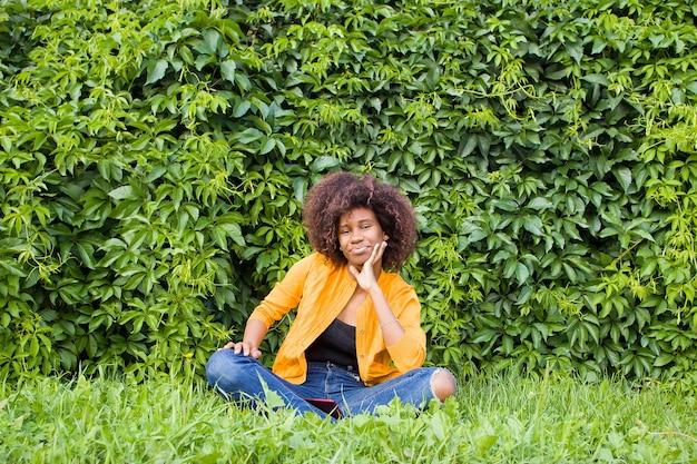 Une femme afro-américaine heureuse et jeune est assise sur les marches à l'extérieur