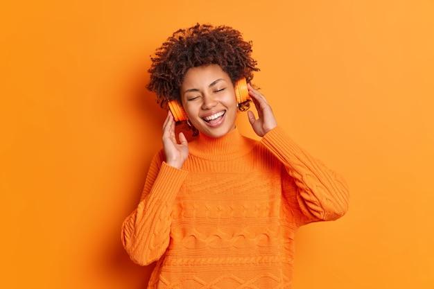Une femme afro-américaine heureuse jouit d'une chanson agréable via des écouteurs stéréo sourit largement garde les yeux fermés a une expression heureuse