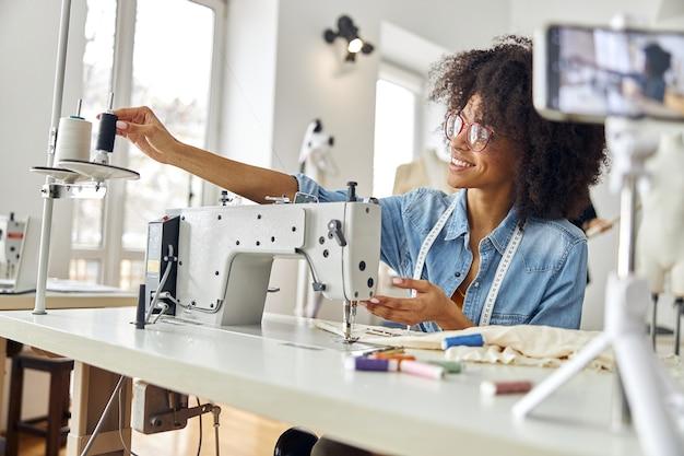 Une femme afro-américaine heureuse met une bobine sur une machine à coudre en train de filmer une nouvelle vidéo en studio
