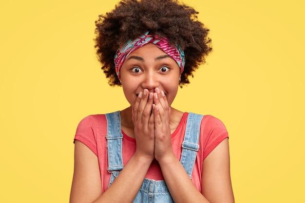 Une femme afro-américaine heureuse rit silencieusement en voyant quelque chose de drôle, se couvre la bouche avec les mains, a une expression faciale heureuse, porte une salopette en denim à la mode, pose à l'intérieur contre un mur jaune
