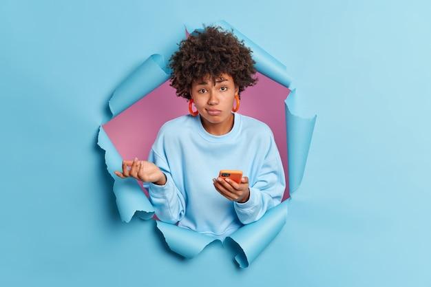 Une femme afro-américaine inconsciente hésitante ne sait pas pourquoi son téléphone ne fonctionne pas ne peut pas résoudre le problème avec le gadget moderne semble désemparé à l'avant habillé avec désinvolture dans un mur de papier bleu déchiré
