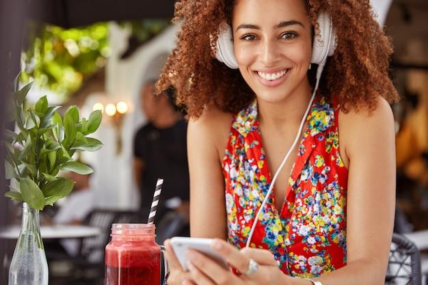 Une femme afro-américaine joyeuse aux cheveux bouclés écoute une composition fraîche dans des écouteurs, profite d'une bonne détente et d'un repos d'été dans un restaurant avec cocktail.