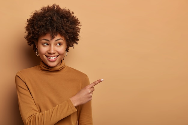 Une femme afro-américaine joyeuse et heureuse indique de côté, promet des marchandises, sourit joyeusement, porte un col roulé marron, pose contre un mur marron. concept publicitaire. nice stuff ça. regarde là-bas