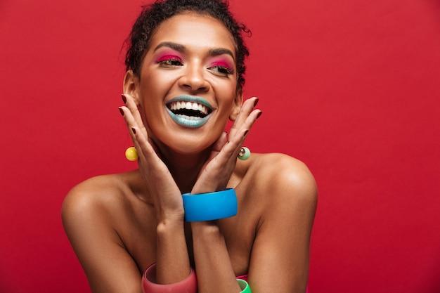 Femme afro-américaine joyeuse multicolore avec maquillage mode souriant et regardant de côté, isolé sur mur rouge