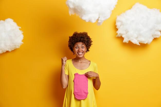 Une femme afro-américaine joyeuse serre le poing et se sent heureuse en découvrant qu'elle aura une fille, tient un maillot de bébé sur le ventre, se dresse contre le jaune avec des nuages au-dessus. concept de grossesse