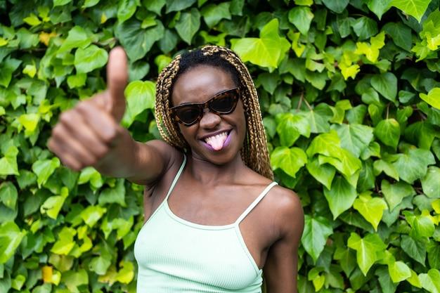 Femme afro-américaine avec des lunettes de soleil faisant un geste heureux avec la main tout en tirant la langue avec un fond de feuilles vertes.