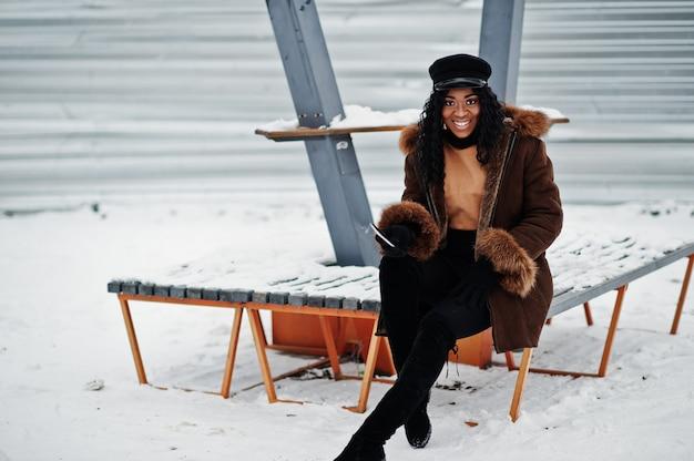 Femme afro-américaine en manteau et casquette en peau de mouton posée à la journée d'hiver sur fond neigeux, assis sur un banc avec téléphone à portée de main.