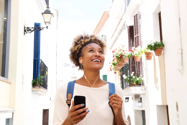 Femme afro-américaine marchant dans la rue et écouter de la musique sur téléphone mobile