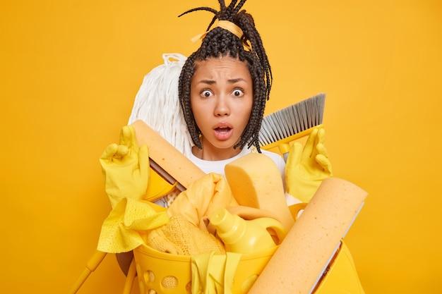 Une femme afro-américaine nerveuse et perplexe avec des dreadlocks regarde choquée