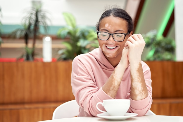 Femme afro-américaine noire avec problème de peau de pigmentation vitiligo intérieur habillé lunettes à capuche rose sitiing table boisson intérieure thé souriant heureux personne positive en attente au restaurant