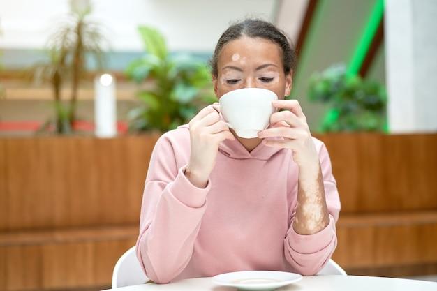 Femme afro-américaine noire avec problème de peau de pigmentation vitiligo intérieur habillé rose hoodie boire thé tasse blanche