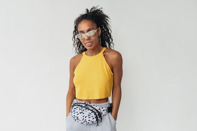 Femme afro-américaine noire en tenue élégante hipster haut jaune sur blanc