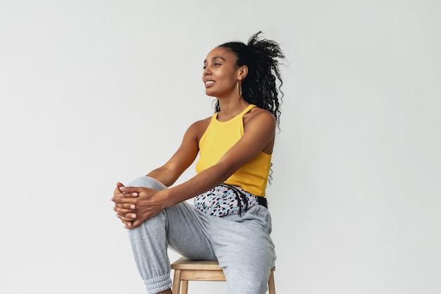 Femme afro-américaine noire en tenue élégante hipster haut jaune sur fond blanc isolé., tendance de la mode estivale, sac banane d'accessoires pour cheveux bouclés souriant heureux