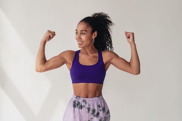 Femme afro-américaine noire en tenue de fitness hipster élégant haut violet et pantalon sur blanc