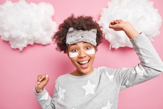 Femme afro-américaine optimiste avec des danses de cheveux bouclés sans soucis bénéficie de bonjour habillé en vêtements de nuit soulève les bras applique des patchs isolés sur mur rose nuages blancs moelleux au-dessus de la tête