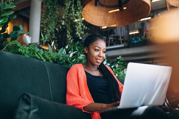 Femme afro-américaine avec ordinateur portable dans un café
