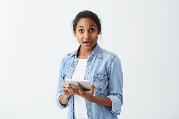 Femme afro-américaine oublieuse avec une chemise bleue attrayante sombre tenant une tablette dans ses mains avec un regard étonné et étonné, ayant complètement oublié quelque chose de sérieux.