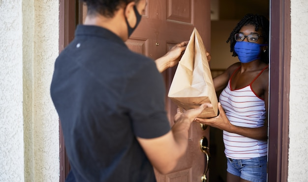 Femme afro-américaine ouvrant la porte pour recevoir l'ordre à emporter tout en portant un masque