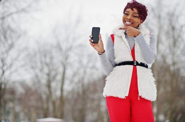 Femme afro-américaine en pantalon rouge et veste de manteau de fourrure blanche posée au jour d'hiver sur fond neigeux, montrer le doigt au téléphone.