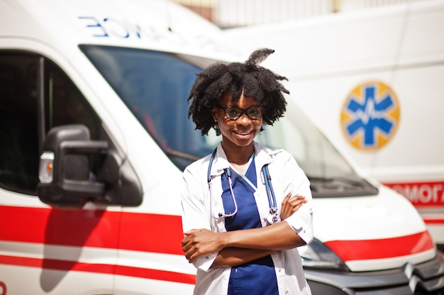 Femme afro-américaine paramédicale debout devant la voiture d'ambulance