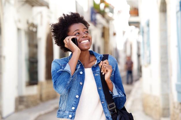 Femme afro américaine parlant au téléphone mobile et souriant à l'extérieur