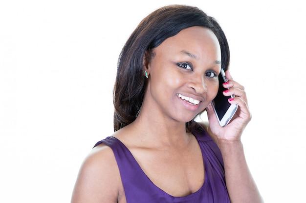 Femme afro-américaine parle sur son téléphone sur fond blanc