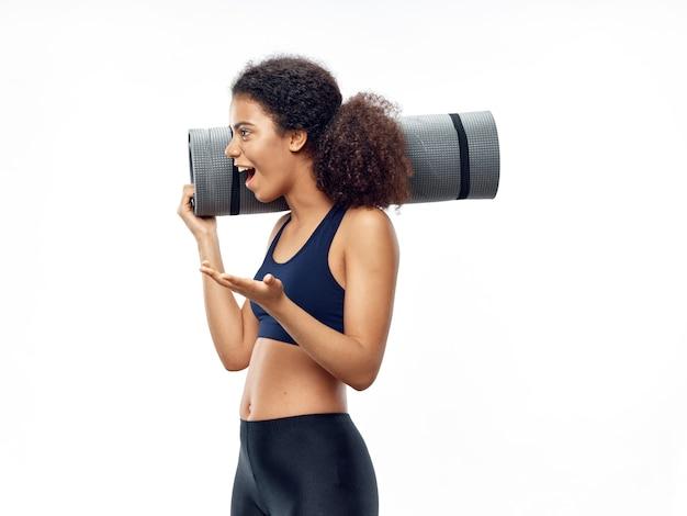 Femme afro-américaine à la peau foncée posant dans un survêtement et faisant du sport